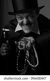 Gentleman in black high hat, in black cape and a cane in his right hand holds a scattering of jewels in his left hand and laughs sarcastically.