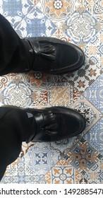 gentleman boots stepping on bohemian floor