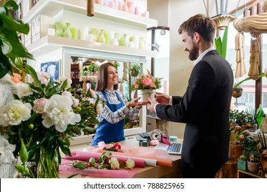 Gentleman bought bouquet at the flower shop. Happy florist working as a cashier, giving an box with flower composition. Beautiful gift for spouse.