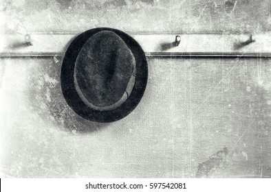 Gentleman felt hat in black on a wooden clothes hanger, textured in grey tones with scratches and stains for a grungy nostalgic feeling with copy space.