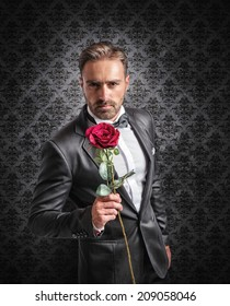 Gentleman gives a red rose on the anniversary