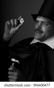 A gentleman in a high hat, black cape and a cane in his hand considering the brilliant crystal.