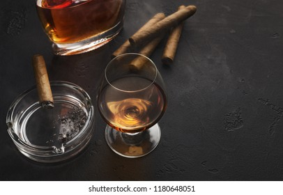 Gentleman luxury entertainment. Cigars and cognac portion with bottle on black table, copy space