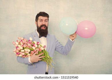 Gentleman making romantic surprise for her. Flowers delivery. Gentleman romantic date. Birthday greetings. Confidence and charisma. Man bearded gentleman suit bow tie hold air balloons and bouquet.