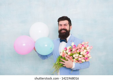 Gentleman romantic date. Birthday greetings. Flowers delivery. For someone special. Man bearded gentleman suit bow tie hold air balloons and bouquet. Gentleman making romantic surprise for her.
