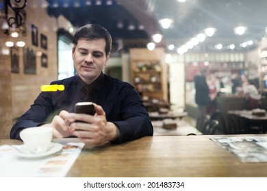 Gentleman sitting at the table using his phone texting and drinking coffee