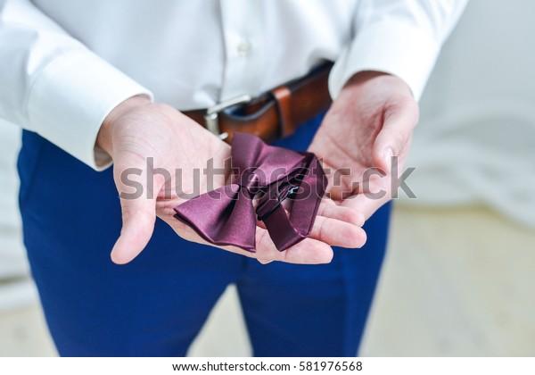 gentleman straightens his sleeves on the costume
