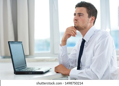 A gentleman in a suit sits at a table in his office an open laptop with a puzzled look