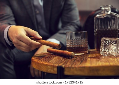 Gentleman takes a cigar from a wooden table with carafe of whisky and glass