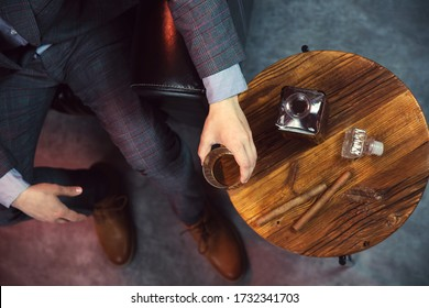 Gentleman takes a glass of whisky and a wooden table with carafe of whisky and cigars. View from the top.