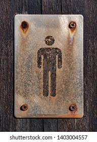 Gentleman toilet sign in old and rustly metallic plate on wooden surface