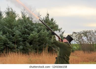 Gentleman  wearing top hat rough shooting with a mussel loading shot gun