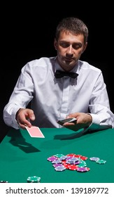 Gentleman in white shirt, playing cards, on black background