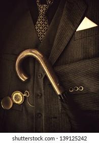 Gentleman's suit with pocket watch and umbrella.Sepia image.