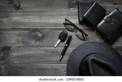 Gentlemen's accessories top view on wooden background with copy space. Hat, money pockets, glassess, car key, pen, diary notebook on wooden plank  background.