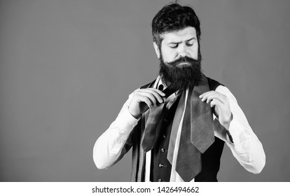 Gentlemens guide. How to choose right tie. Classic style. How to match necktie with shirt and suit. Man bearded hipster hold few neckties on blue background. Guy with beard choosing necktie.