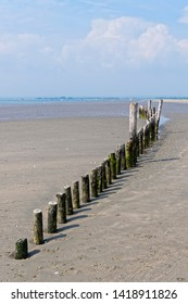 Gently curving row of old wooden posts on West Wittering beach at low tide