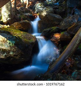 gently flowing mountain stream in spring with dappled sunlight