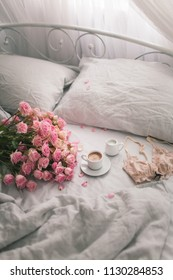 Gently pink roses lie on the gray linen bedding with coffee. Romantic mood of the morning