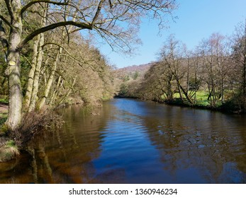 Gently rippled water of the River Derwent flowing between tree lined banks in the Derbyshire Countryside.