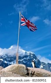 Gentoo Penguin beneath British flag at Port Lockroy, Antarctica