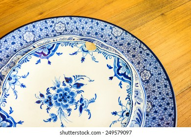 Genuine antique dinner plates from Delft on a wooden table