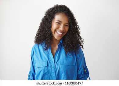 Genuine human facial expressions, emotions and feelings. Isolated picture of cheerful relaxed young dark skinned lady with dazzlign ultrawhite smile laughing at joke, posing isolated in studio