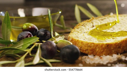 Genuine Italian organic oil cold pressed in slow motion falls on organic bread. concept of nature and healthy food, healthy and natural. fresh olives and Tuscan Italian oil
