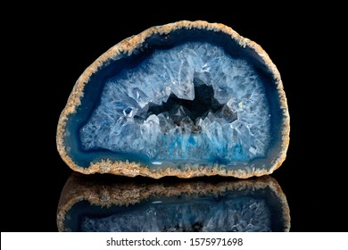 Geode with crystals of blue color. Quartz geode with transparent crystals on a black mirror background.