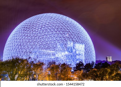 A geodesic dome next to an old tower surrounded by a colorful autumn forest in Montreal, Quebec, Canada.