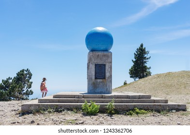 """Geodesic sign """"Ai-Petri Meridian"""". Russia, Republic of Crimea. 06.13.2018. Geodesic sign installed on top of Mount Ai-Petri in 1913. On the average plan is a girl looking into the distance at sea"""