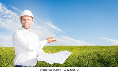 Geodesist with drawings on ground for building building. Builder in white helmet and project documentation on green meadow. soil scientist examines earth and soil Engineer points to construction site