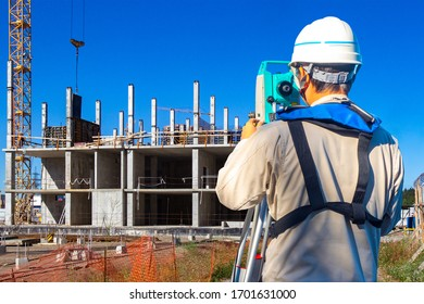 Geodetic surveys during construction. Construction work on a summer day. Concept - construction of multi-storey buildings. Builder a tachometer in his hands. Builder sent a tachometer to the building