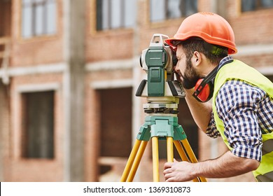 Geodetic works. Surveyor engineer in protective wear and red helmet using geodetic equipment at construction site. Professional equipment.