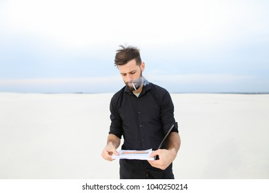 Geographer male smoking, young man come to seaside to carry out research. Bearded guy with short fair hair standing on sand viewing papers in black folder looking around. Concept of science an