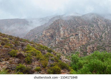 geographical detail of folded mountain cliff in a clouded landscape