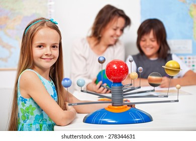 Geography class - little girl learning about the solar system using a scale model