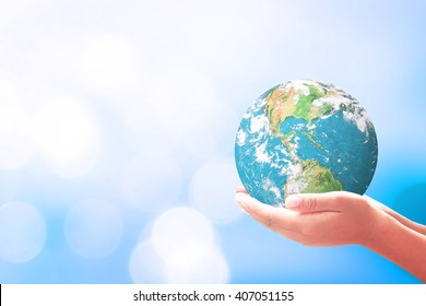 Geography concept: Human hands holding the earth globe over blurred blue nature background. Elements of this image furnished by NASA