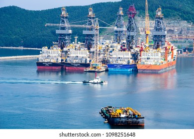 GEOJE ISLAND, SOUTH KOREA - MAY 20, 2018 : Tugboat sails pass driil ships in the Bay of Daewoo Shipbuilding and Marine Engineering (DSME) in Okpo city, South Korea.
