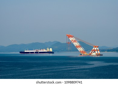 GEOJE ISLAND, SOUTH KOREA - MAY 13, 2018 : Large liquefied natural gas (LNG) carrier and Very large floating crane anchor in the harbour near Samsung Heavy Industries or SHI in Geoje island.
