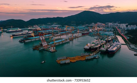 Geoje, South korea - October 2017 : High angle view of Daewoo shipyard in Okpo city of Geoje island. Scenery consist of many comercial ship, large crand, ocean, mountain and blue sky with cloud.