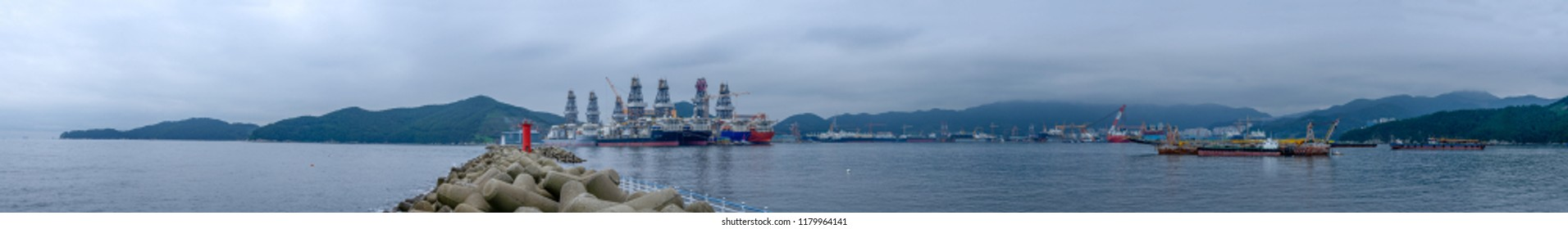 GEOJE, SOUTH KOREA - SEPTEMBER 15, 2018: Bay of Daewoo Shipbuilding and Marine Engineering (DSME) in Okpo with wave breaking, marine engineering facilities, ships and offshore platforms in the evening