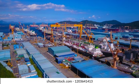 Geoje, South korea - September 2018 : Aerial view of Daewoo shipyard in okpo city, South korea. Scenery consist of shipyard inside the bay, commercial ship, platform, heavy crane and building.