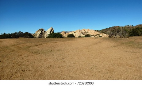 Geological formations towering above a dry field, California