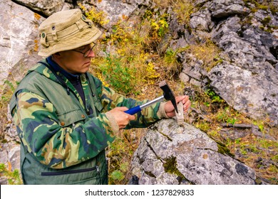 geologist splitting a mineralogical sample with a geological hammer