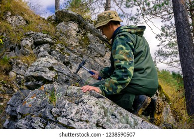 geologist using a geological hammer takes a rock sample outdoor