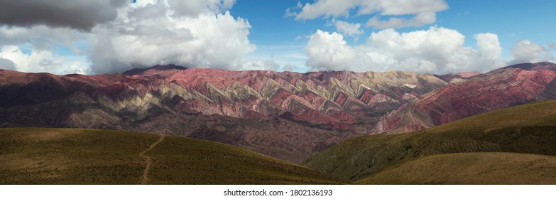 Geology. Andes mountain range. Panorama view of a footpath in the yellow grassland leading to the colorful Hornocal mountain under a dramatic cloudy sky in Humahuaca, Jujuy, Argentina.