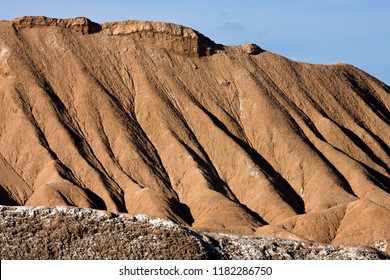 Geology - Water erosion of soft sedimentary rock in the Atacama Desert in Chile - The white deposit on the rocks in the foreground is salt
