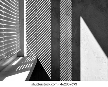 Geometric black and white composition. The plane of the plaster wall with a structural graphic shadow falling from the blinds. Horizontal view.