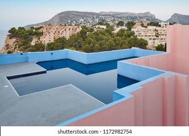 Geometric building swimming pool. Red wall, La manzanera. Calpe, Spain
